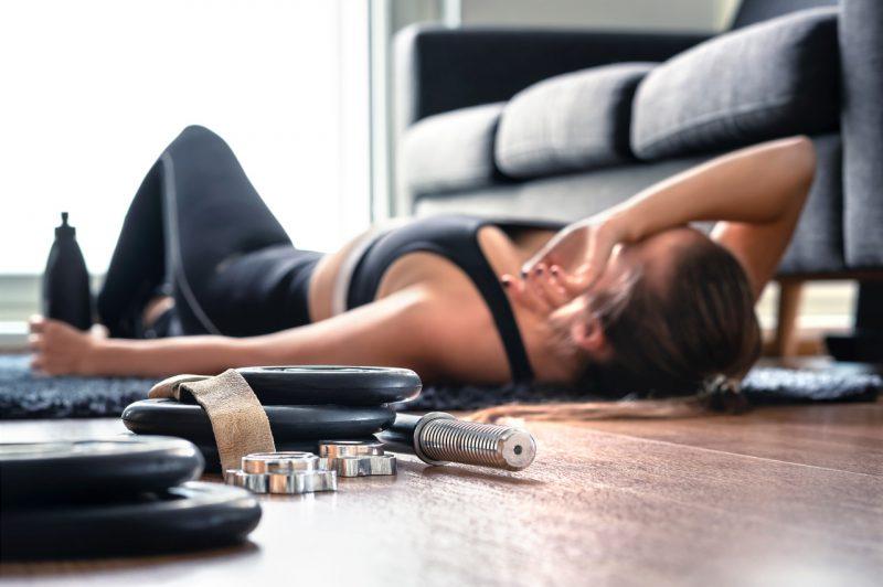 Przetrenowanie - wyczerpana młoda kobieta po treningu.